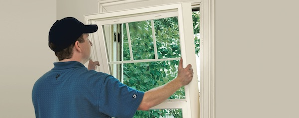 a window installer is installing new windows on a home